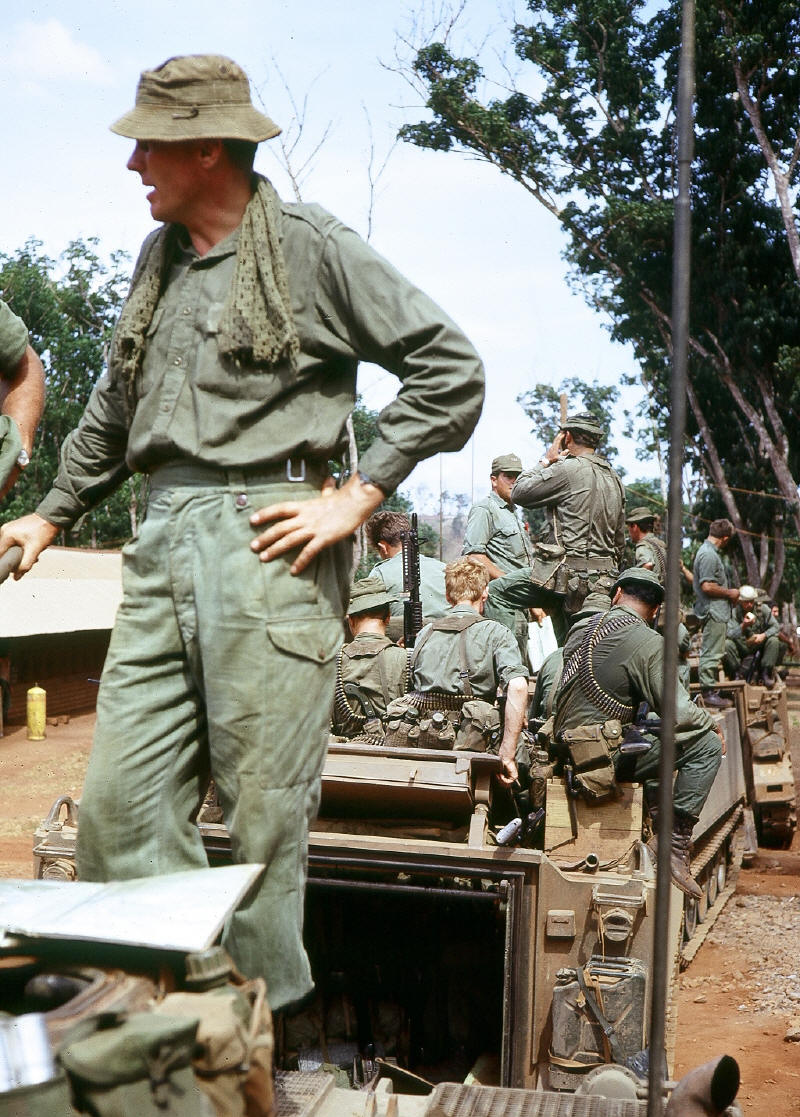 It was common for troops to ride on top of APC - Maj Evan Torrance & Coy HQ mounting APC before departure Nui Dat [Stock]