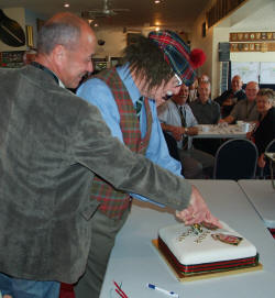Craig Cocker [thought to be youngest at the time] and Doug Mackintosh [oldest] cut the reunion cake [Binning]  Doug was displaying his Scotish heritage....