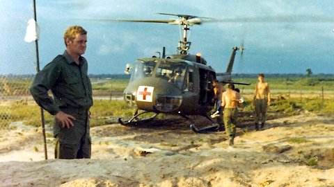 Goodman with CASEVAC chopper behind, others carrying injured Vietnamese kids to chopper [Jane]